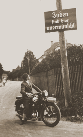 "A motorcyclist reads a sign stating ""Jews are not welcomed here."" Germany, ca. 1935. — US Holocaust Memorial Museum, courtesy of Margaret Chelnick"
